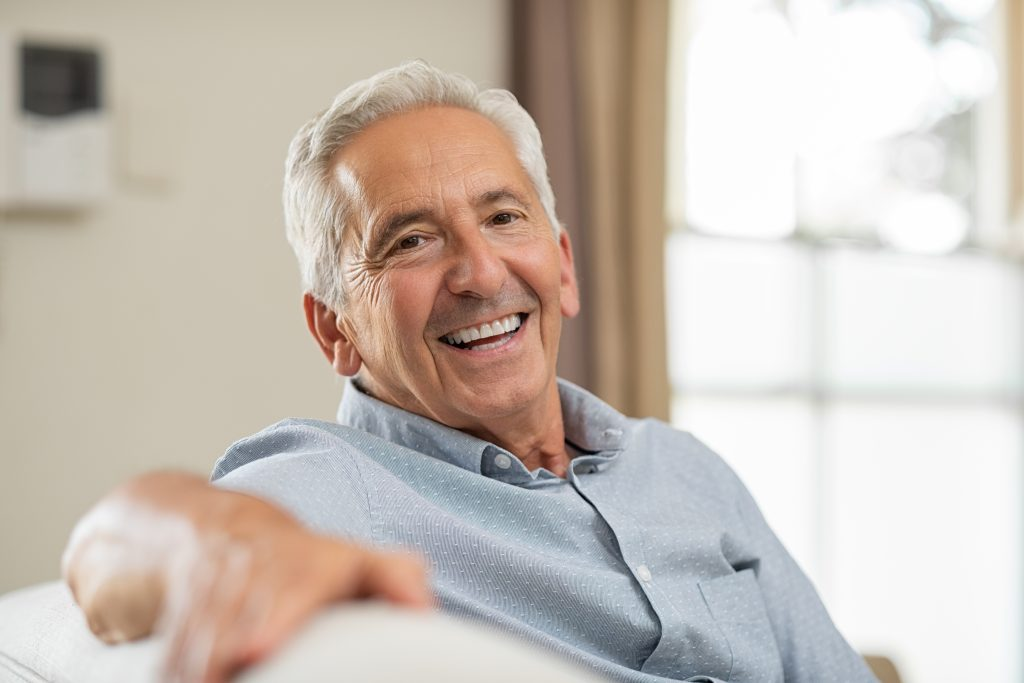 older gentleman sitting on couch smiling