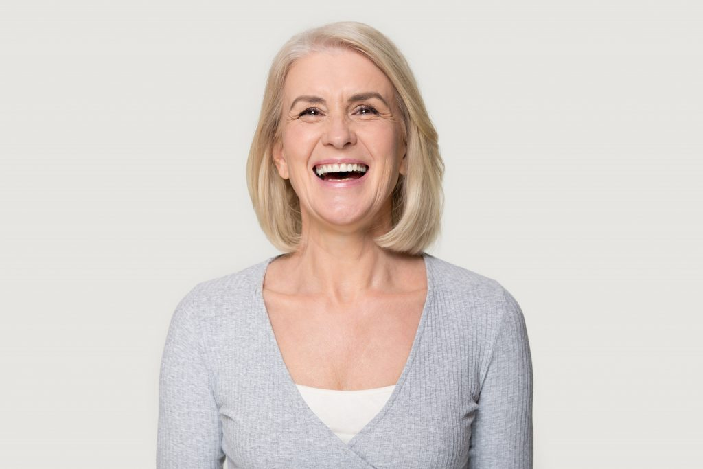 woman in gray sweater laughing