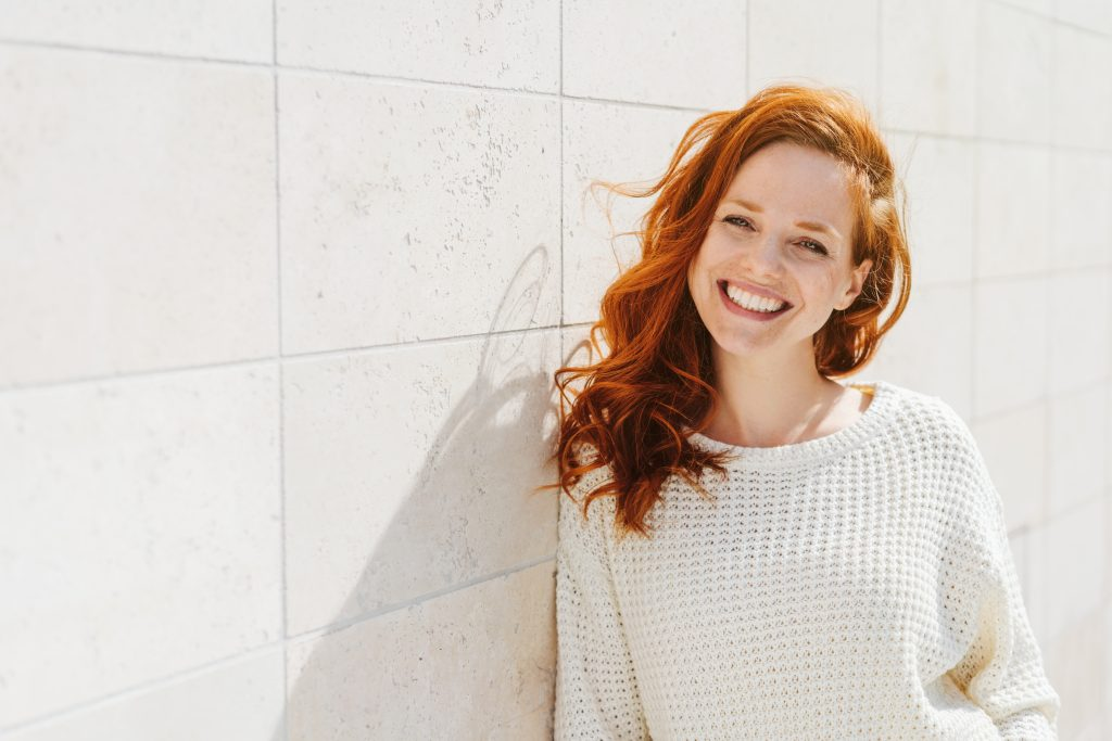redheaded woman in white sweater smiling