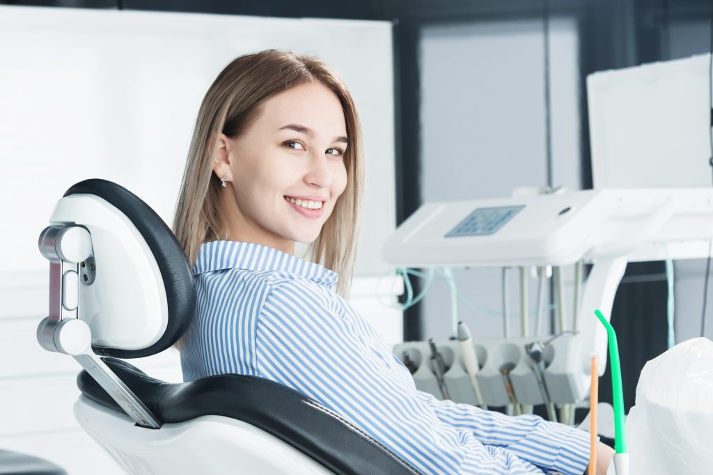 woman in dental chair waiting for dental exam to begin