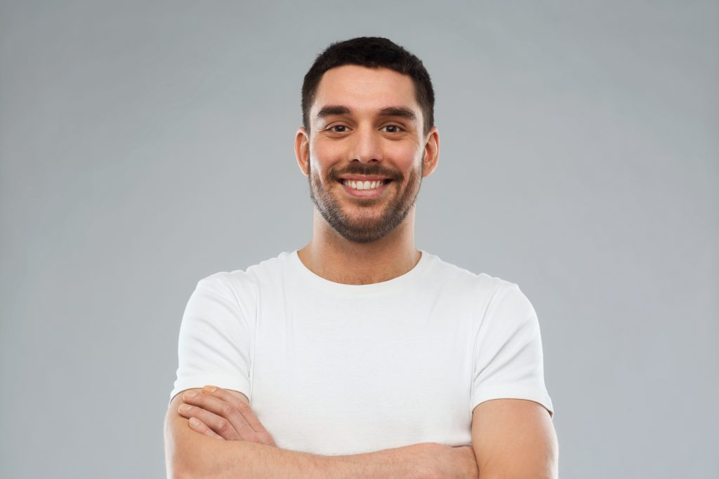 man in white shirt with crossed arms smiling