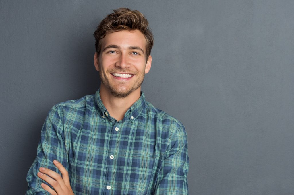 young man in checkered shirt smiling