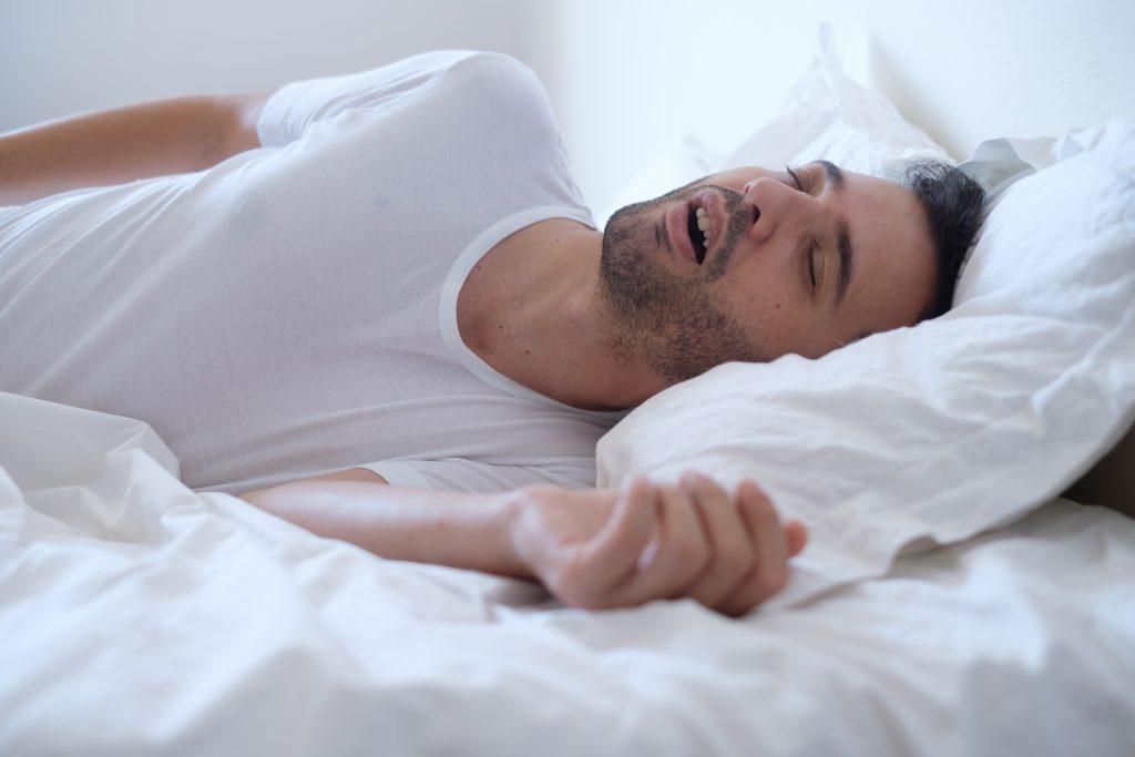 man laying in bed snoring